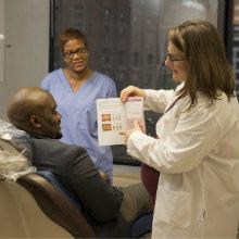 A dentist explaining a dental procedure to her patient