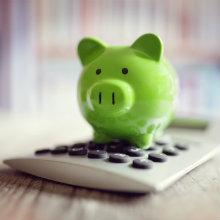 green piggy bank sitting on top of a calculator